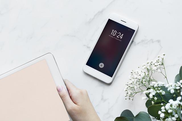 女性の仕事デスクにスマートフォンが置いてある